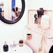 une salle-de-bains rose, noir et cuivre